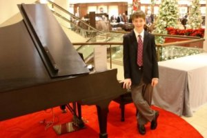 Eric Cameron beside a piano at Nordstrom's